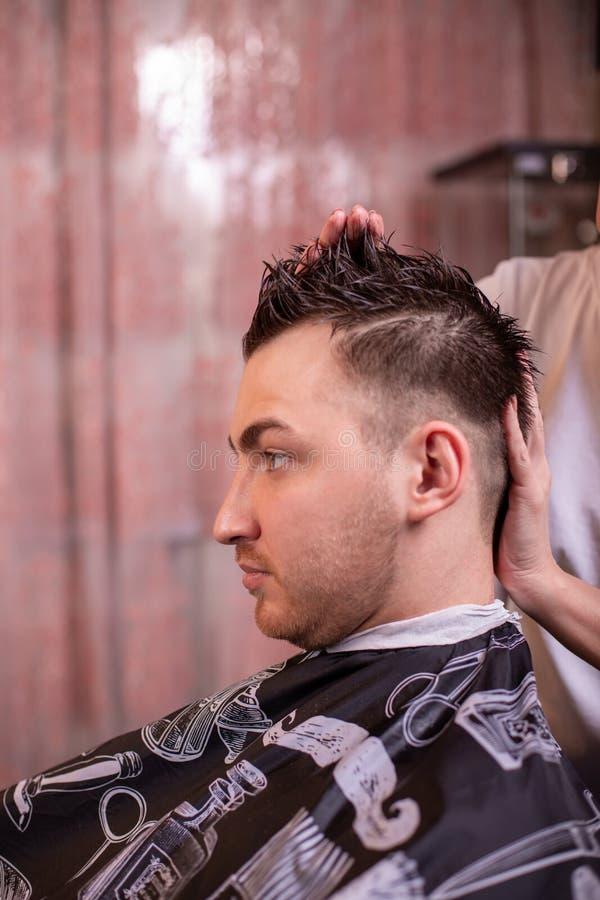 O mestre põe o cabelo de um homem em um barbeiro, um cabeleireiro faz um penteado para um homem novo com a ajuda do gel imagem de stock