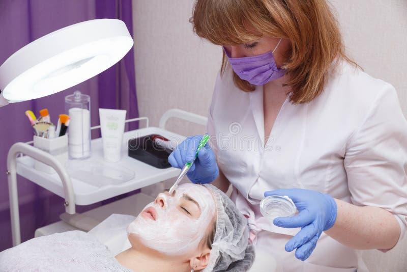 O mestre põe uma máscara branca com uma escova sobre a cara de uma jovem mulher que encontra-se na tabela imagens de stock