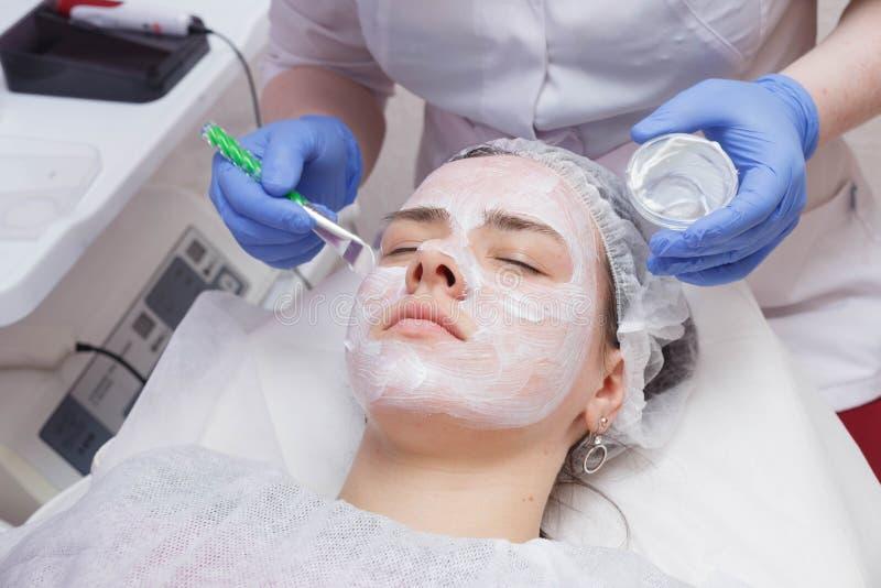 O mestre põe uma máscara branca com uma escova sobre a cara de uma jovem mulher que encontra-se na tabela fotos de stock