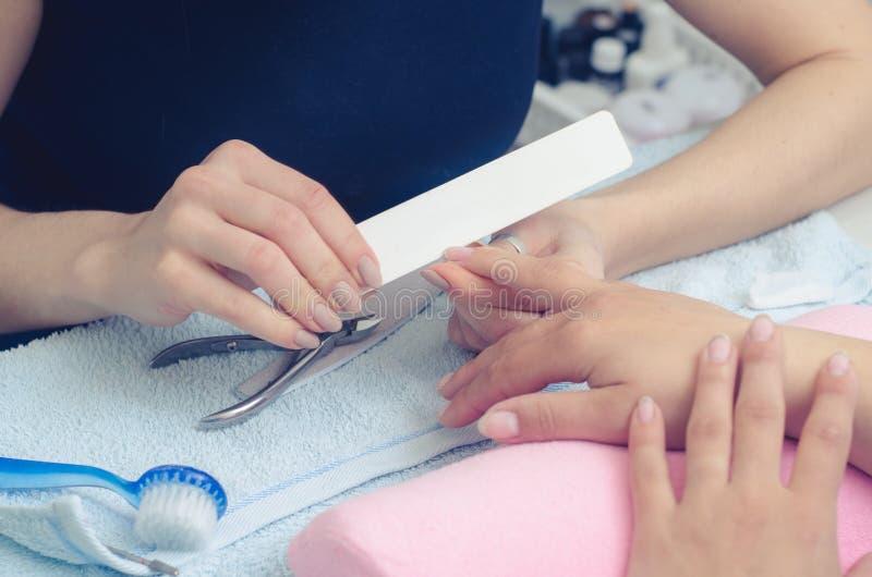 O mestre prepara os pregos para o tratamento de mãos fotografia de stock