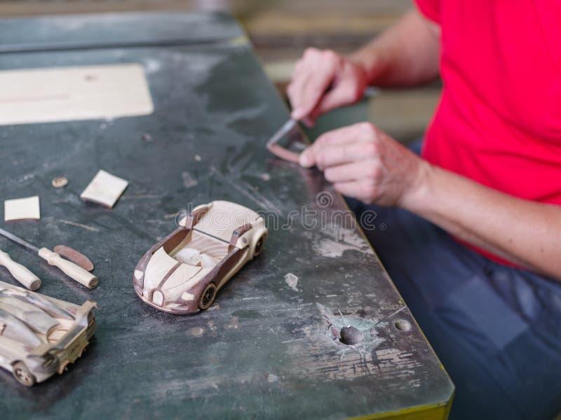 O mestre recolhe um modelo de madeira do carro foto de stock