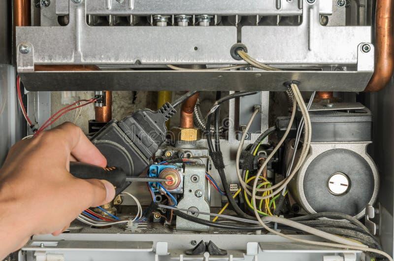 O mestre repara a parte eletrônica da caldeira do aquecimento de gás fotografia de stock royalty free