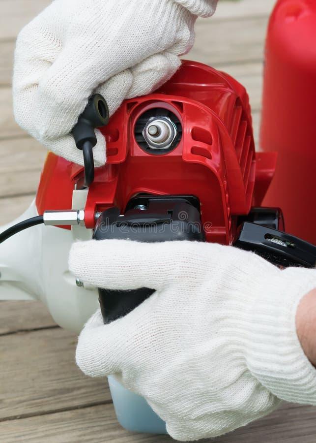 O mestre verifica a vela de ignição dentro do lawnmower, close-up imagem de stock royalty free
