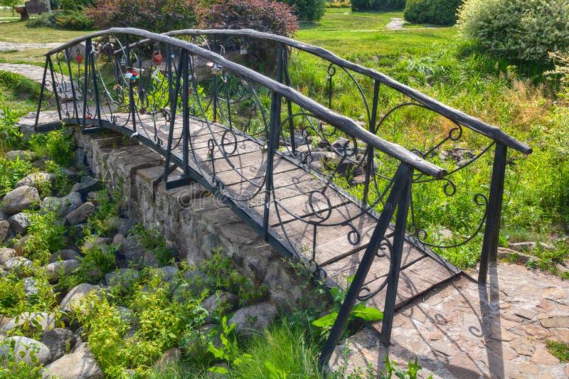 O metal bonito forjou a ponte em um parque consagrado pelo sol imagem de stock royalty free