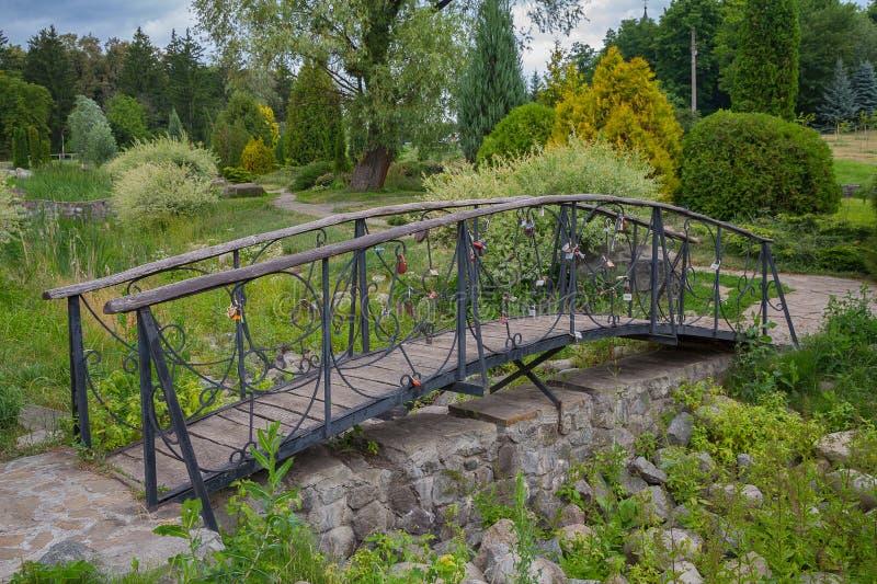 O metal bonito forjou a ponte em um parque consagrado pelo sol imagem de stock