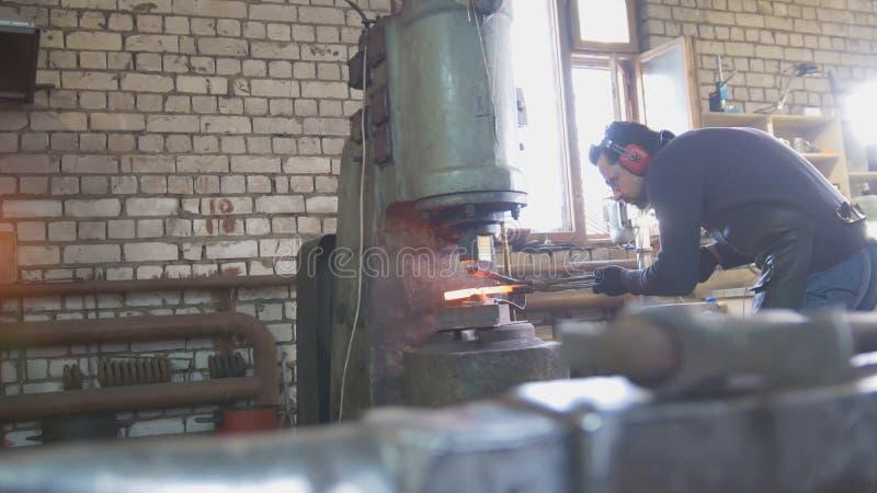 O metal derretido é processado sob a pressão nas mãos de um ferreiro, ângulo largo foto de stock
