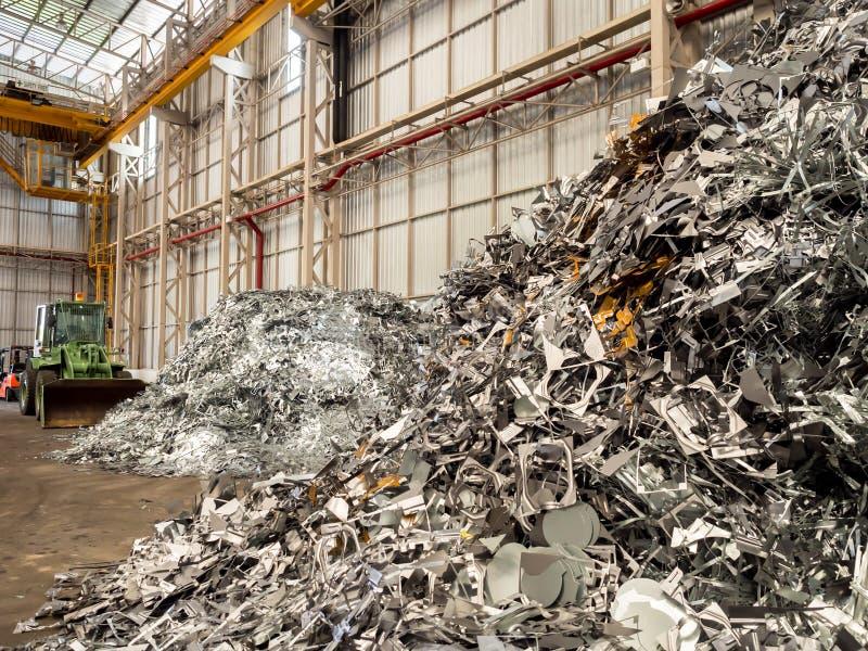 O metal e o alumínio desfazem-se da pilha e a escavadora recicla dentro a fábrica foto de stock