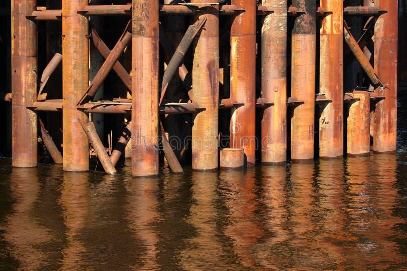 O metal oxidado conduz na água, apoios da construção de ponte velha foto de stock