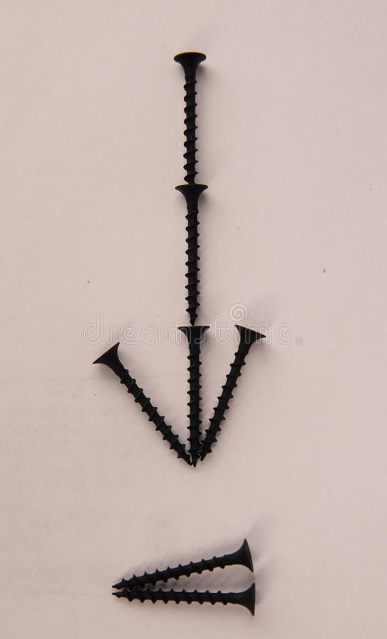 O metal parafusa com a seta no fundo branco fotografia de stock