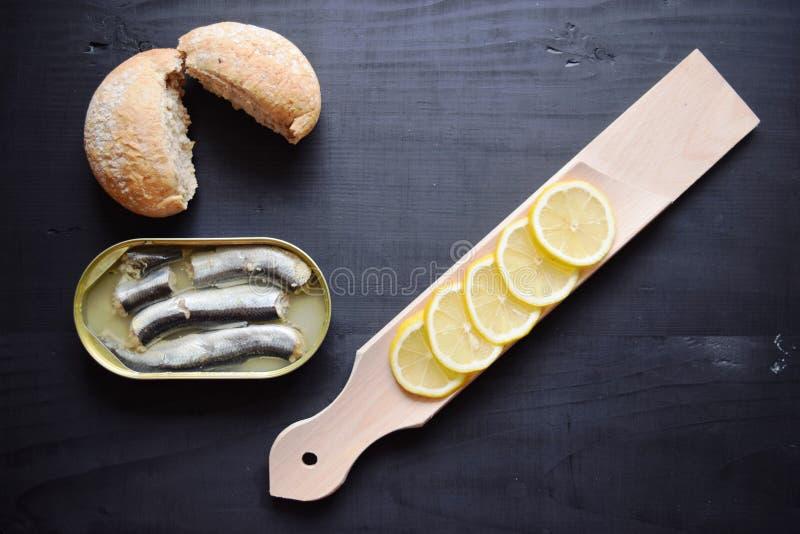 O metal pode com os peixes conservados dos arenques, arenques postos de conserva enlatados, lata de lata aberta, vista superior imagem de stock