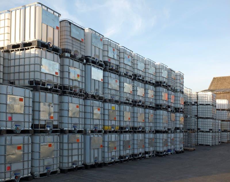 O metal usado moldou os recipientes de maioria intermediários empilhados nas páletes que esperam para ser limpado ou reciclado em imagens de stock