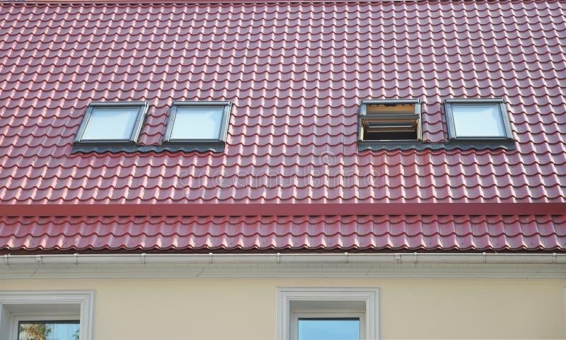 O metal vermelho telhou o telhado com trapeiras novos, o telhado Windows, as claraboias, o sistema da calha da chuva e a proteção fotografia de stock royalty free