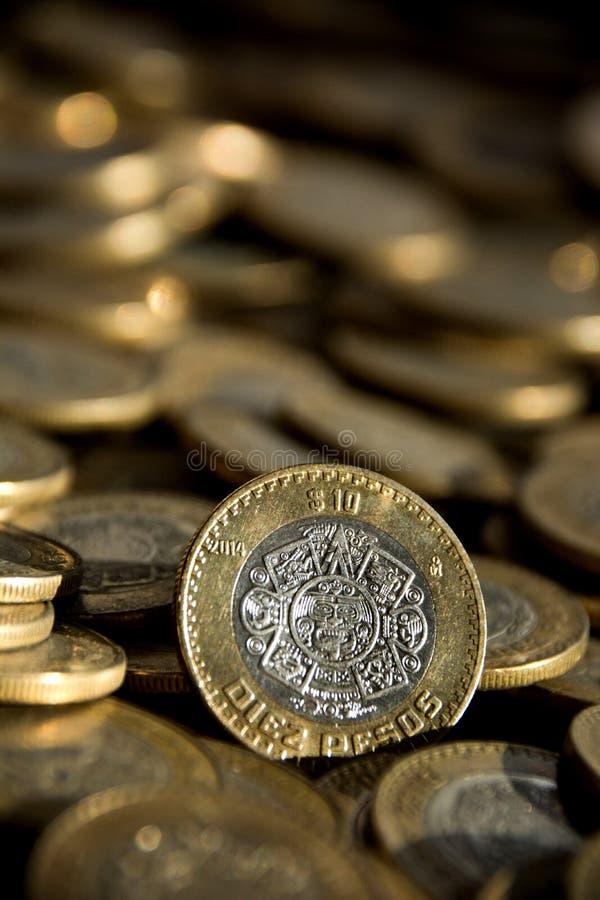 O mexicano 10 pesos inventa no primeiro plano, com muito mais moedas no fundo fotos de stock