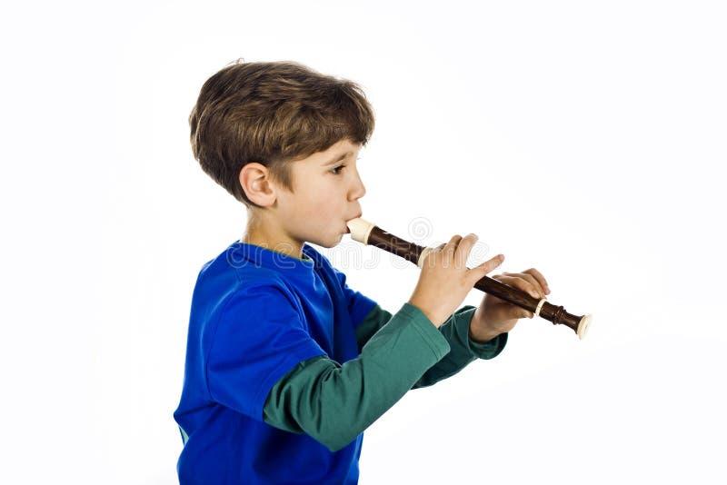 O miúdo e uma flauta foto de stock