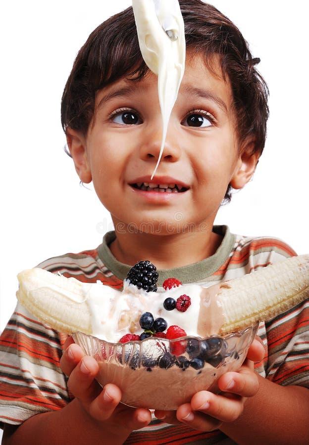O miúdo muito bonito está a ponto de comer a USC misturada muito doce imagem de stock royalty free