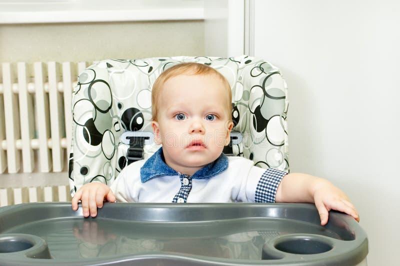 O miúdo senta-se em um highchair imagem de stock