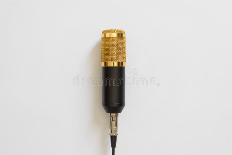 O microfone amarelo preto com o fio em um fundo branco minimalism Copie o espaço para o texto fotografia de stock royalty free