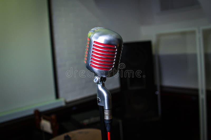 O microfone está na fase em um clube noturno O cantor guarda e canta no microfone Luz brilhante do brilho do clube no MIC imagens de stock
