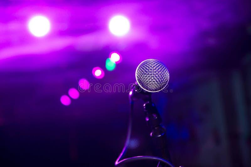 O microfone sob as luzes da fase com bokeh imagem de stock