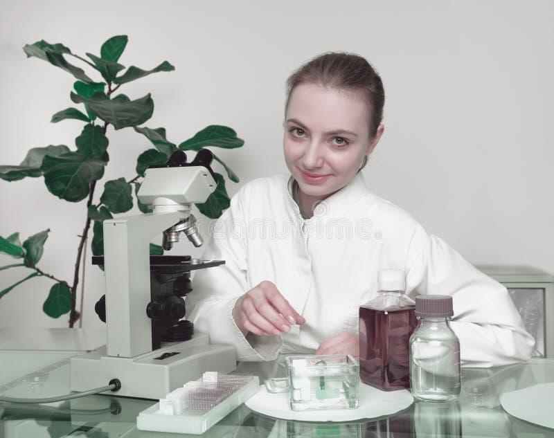 O microscopist fêmea novo sorri no visor imagens de stock royalty free