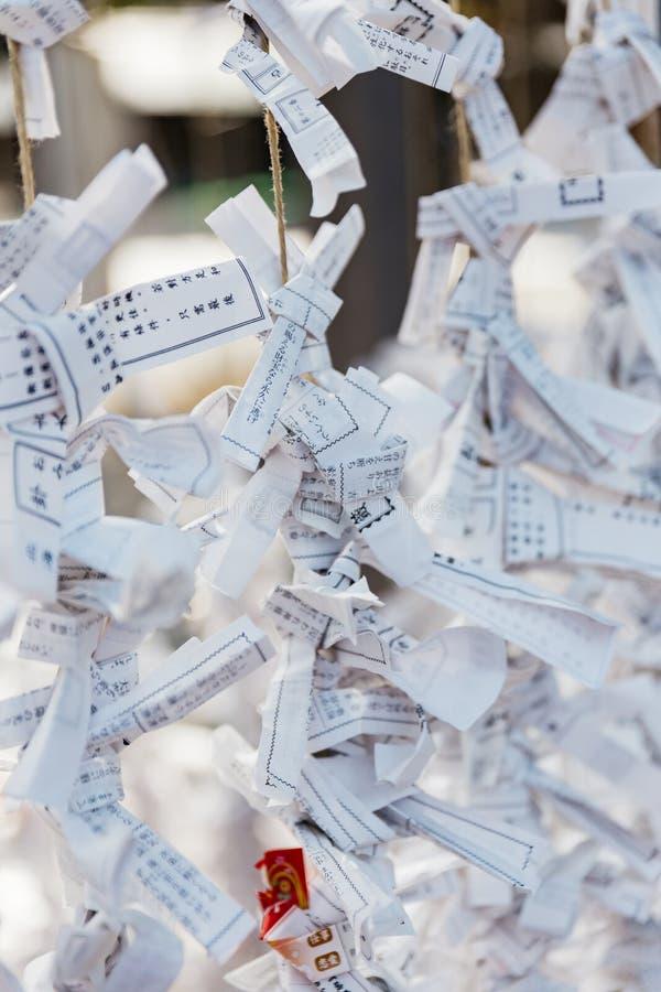 O-mikuji的关闭是在纸小条写的任意时运在神道圣地,并且佛教寺庙在北海道祀奉 免版税库存照片