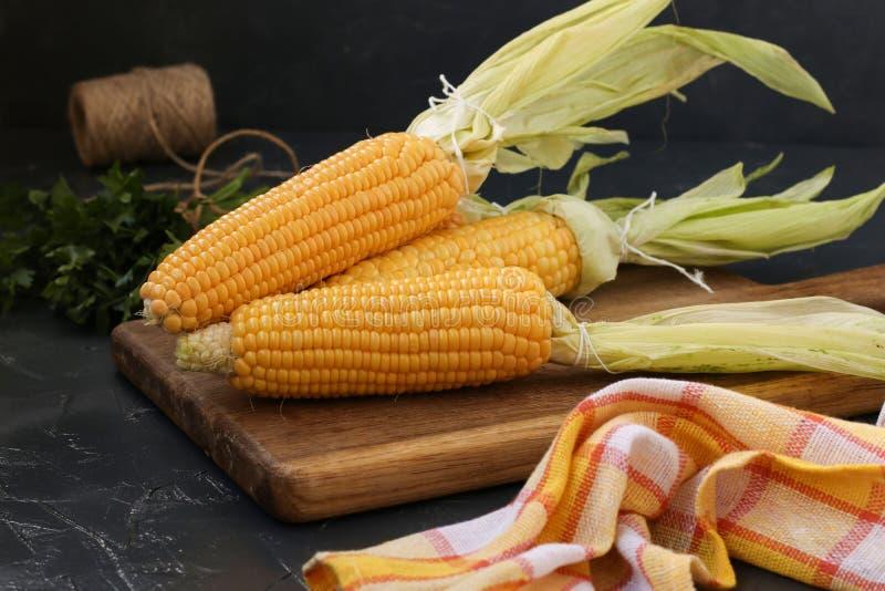 O milho fresco, limpado é ficado situado em uma placa de madeira em um fundo escuro imagem de stock royalty free