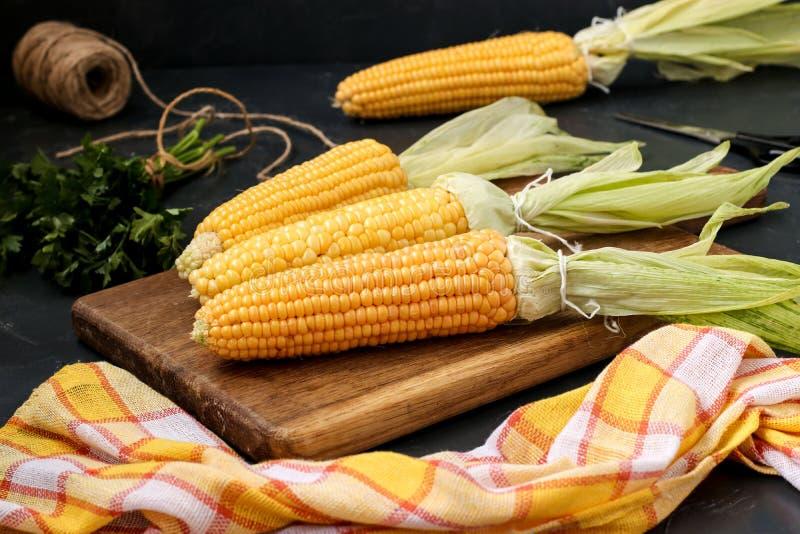 O milho fresco, limpado é ficado situado em uma placa de madeira em um fundo escuro imagens de stock