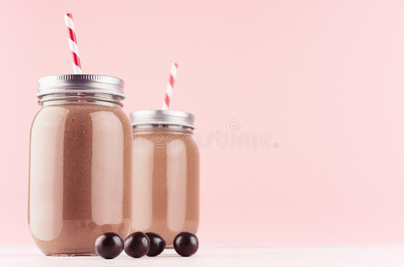 O milk shake do chocolate doce em uns frascos antiquados decorou bolas dos doces, palhas, tampões de prata no fundo cor-de-rosa p foto de stock