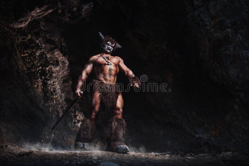 O minotaur irritado do homem do bodyart com o machado na caverna imagens de stock royalty free