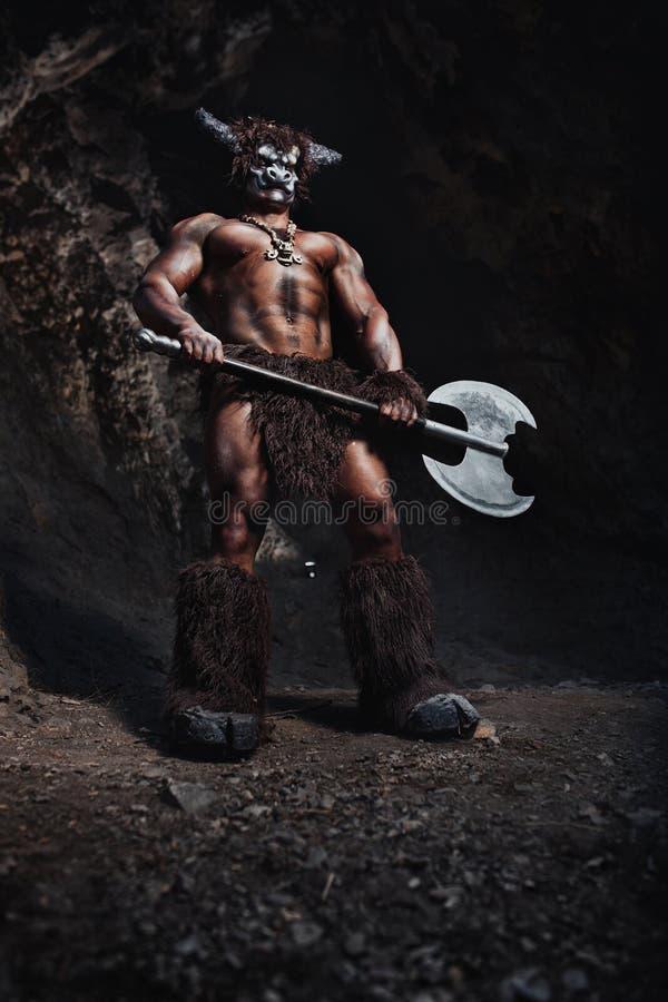 O minotaur irritado do homem do bodyart com o machado na caverna fotos de stock royalty free