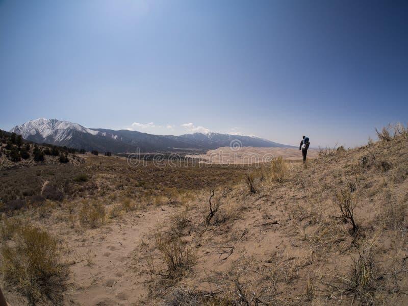 O mochileiro anda ao longo de Sandy Path nas grandes dunas de areia P nacional fotografia de stock