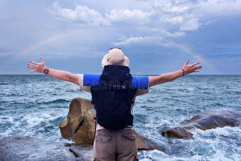 O mochileiro com mochila preta espalha as mãos ao expressi do arco-íris imagem de stock royalty free