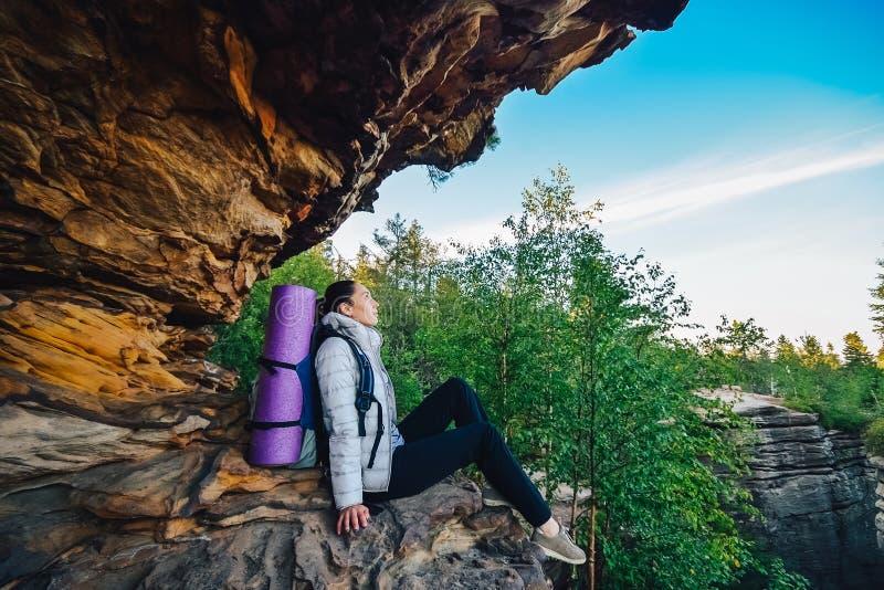 O mochileiro da jovem mulher aprecia a vista no pico de montanha fotografia de stock royalty free
