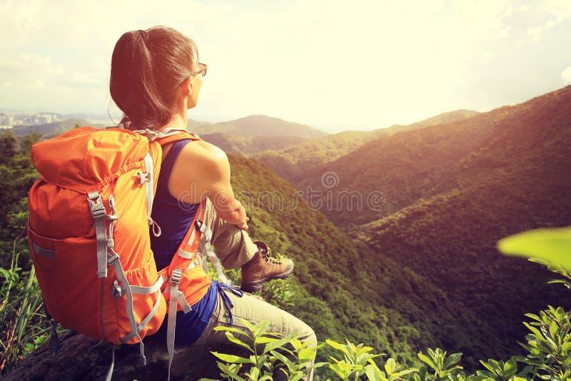 O mochileiro da mulher aprecia a vista no pico de montanha imagem de stock royalty free
