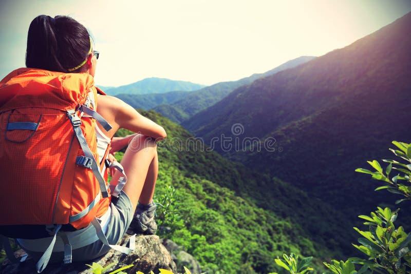 O mochileiro da mulher aprecia a vista no pico de montanha foto de stock