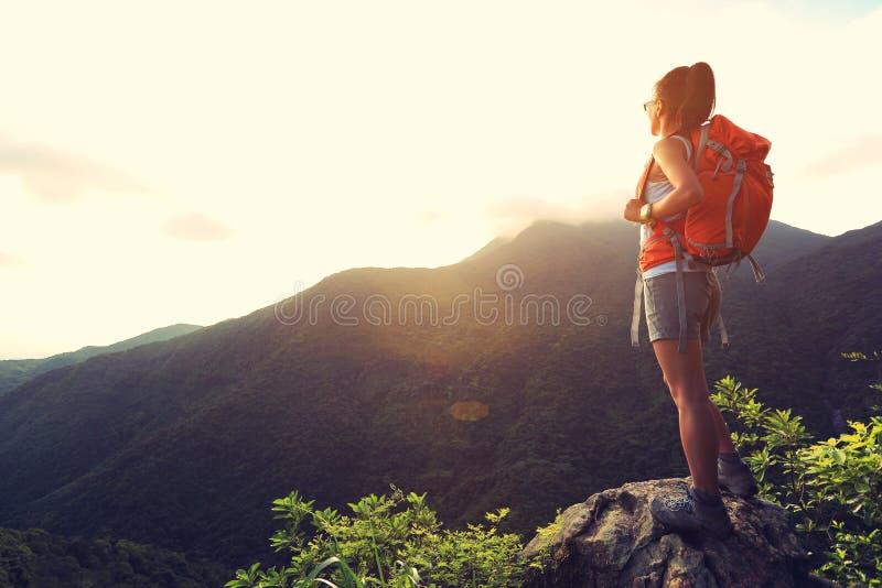 O mochileiro da mulher aprecia a vista no pico de montanha imagens de stock royalty free
