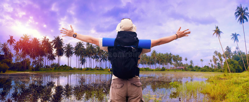 O mochileiro espalha as mãos que expressam a felicidade no landsc tropical imagens de stock