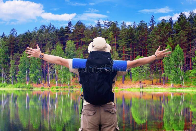O mochileiro espalha as mãos que expressam a felicidade que olha o pinho FO imagens de stock royalty free