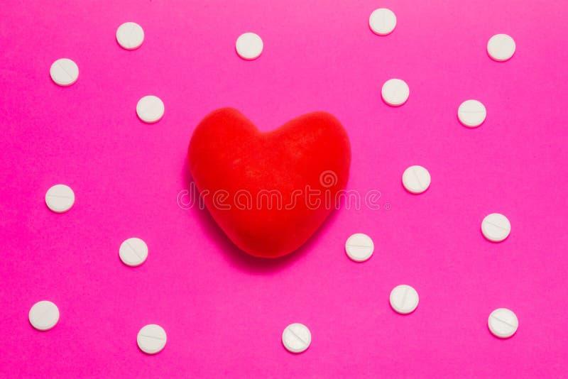 O modelo anatômico 3D do coração está sobre o fundo cor-de-rosa, rodeado por pílulas brancas como pontos poca de ornamento Concei imagem de stock royalty free