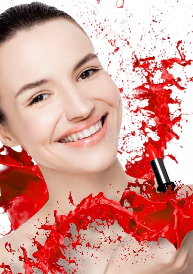 O modelo bonito com pintura do tubo do batom espirra imagem de stock
