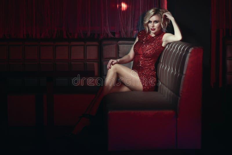 O modelo bonito com provocante compõe o vestido cabido curto vermelho vestindo da lantejoula que relaxa no sofá quadrado no clube foto de stock