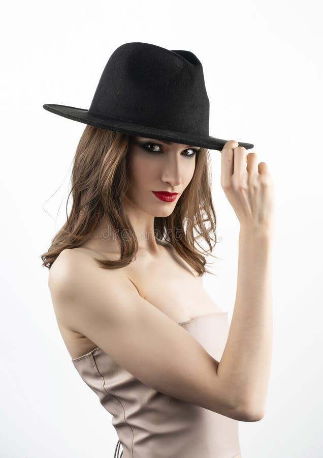 O modelo bonito da menina com bordos vermelhos prepara e sorrisos despidos dos ombros e toca no chapéu negro vestido em sua cabeç imagem de stock
