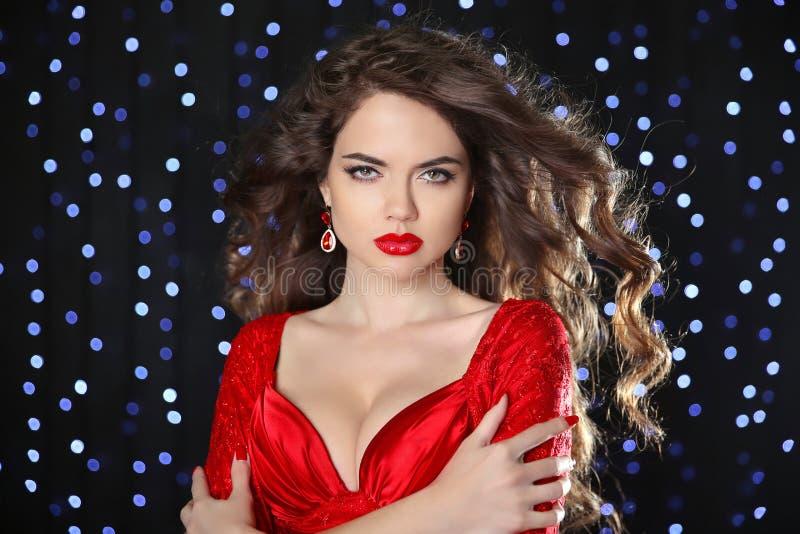 O modelo bonito da menina com marrom longo ondulou o cabelo e os bordos quentes nós imagens de stock royalty free