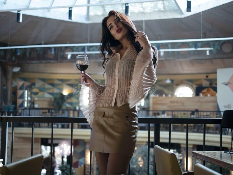 O modelo bonito da menina com pés longos em uma saia curto está estando com um vidro em um restaurante imagens de stock royalty free