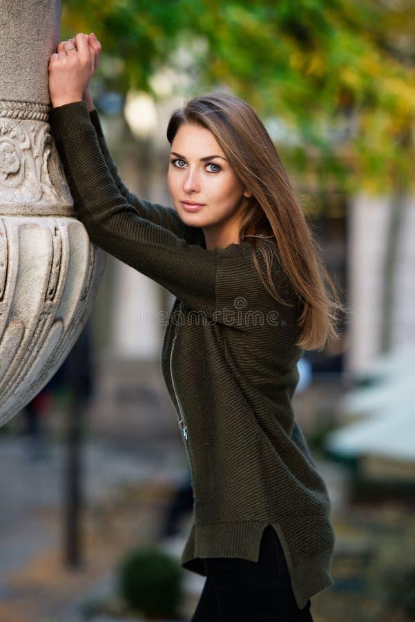 O modelo bonito da mulher vestiu-se em um casaco de lã verde morno que levanta fora em um parque da cidade imagens de stock