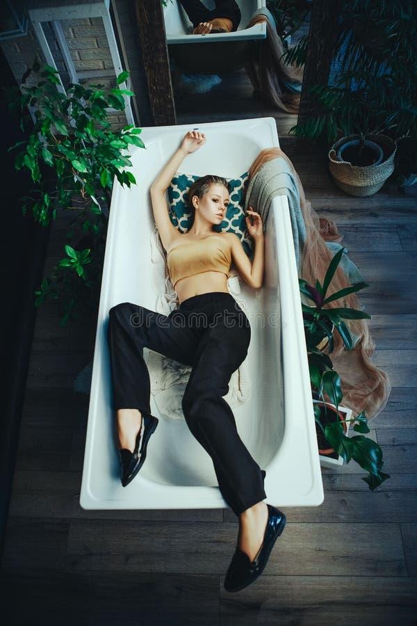 O modelo bonito est? levantando em um banheiro com composi??o de prata criativa imagens de stock