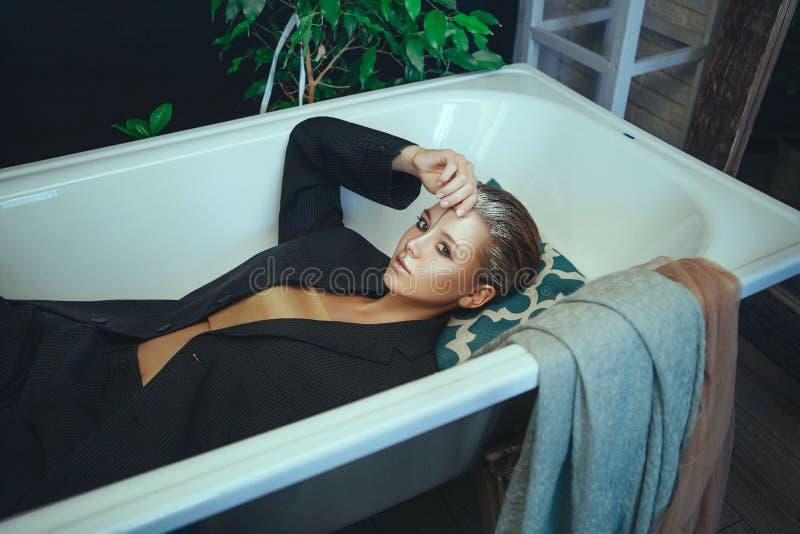 O modelo bonito est? levantando em um banheiro com composi??o de prata criativa foto de stock royalty free