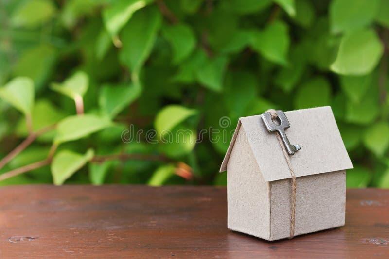 O modelo da casa do cartão com chave contra o verde sae do fundo Compra, aluguel e conceito dos bens imobiliários do país da cons imagens de stock