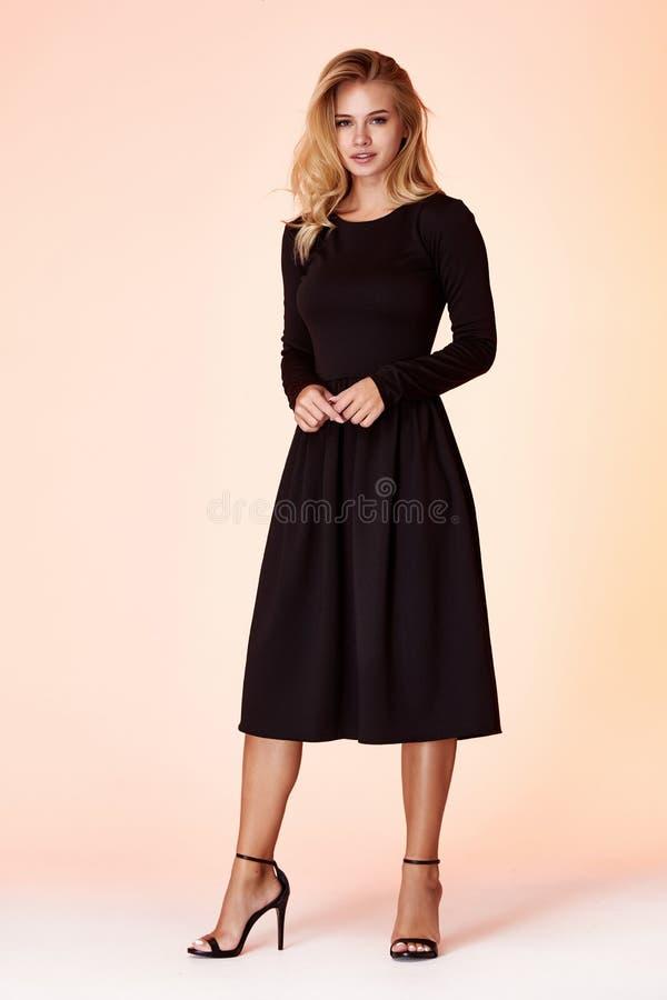 O modelo da mulher da beleza veste o estilo formal ocasional do escrit?rio do vestido magro preto ? moda da roupa da tend?ncia do imagens de stock