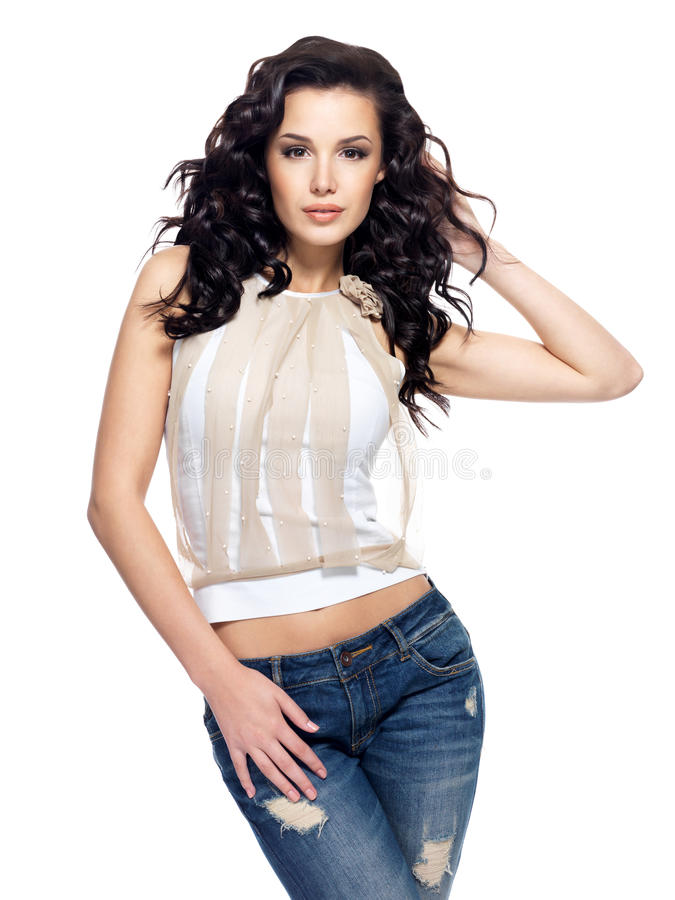 O modelo de forma com cabelo longo vestiu-se na calças de ganga imagens de stock